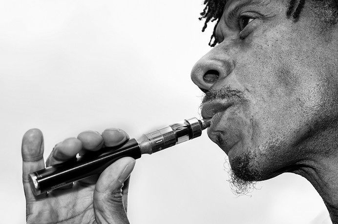 An Afro European mane is looking into the camera whilst inhaling on an electronic cigarette.